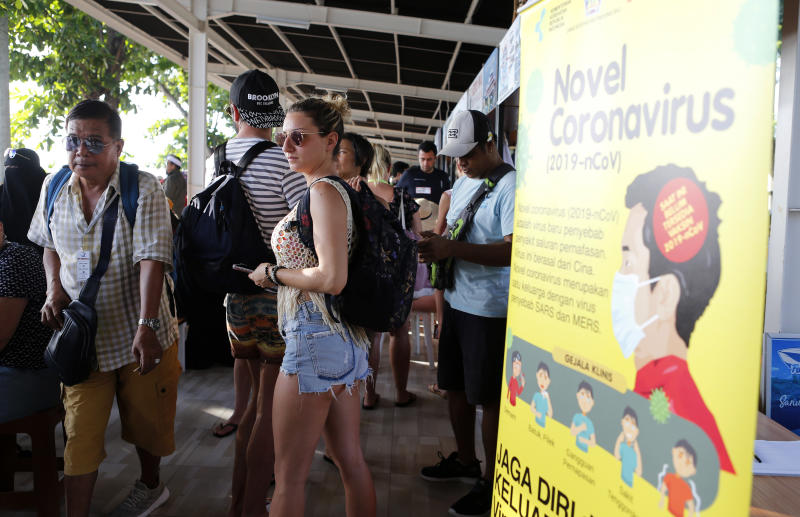 Photo shows foreign tourists standing near an information banner on the coronavirus at a harbour as they wait for their departure in Bali, Indonesia.