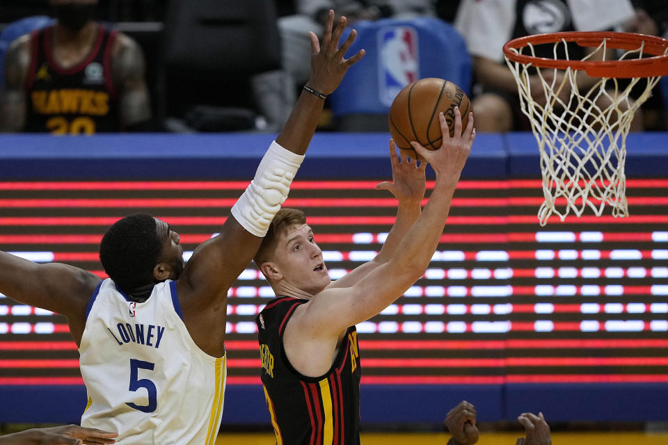 Atlanta Hawks guard Kevin Huerter (3) drives past Golden State Warriors center Kevon Looney (5) during the first half of an NBA basketball game in San Francisco, Friday, March 26, 2021. (AP Photo/Tony Avelar)
