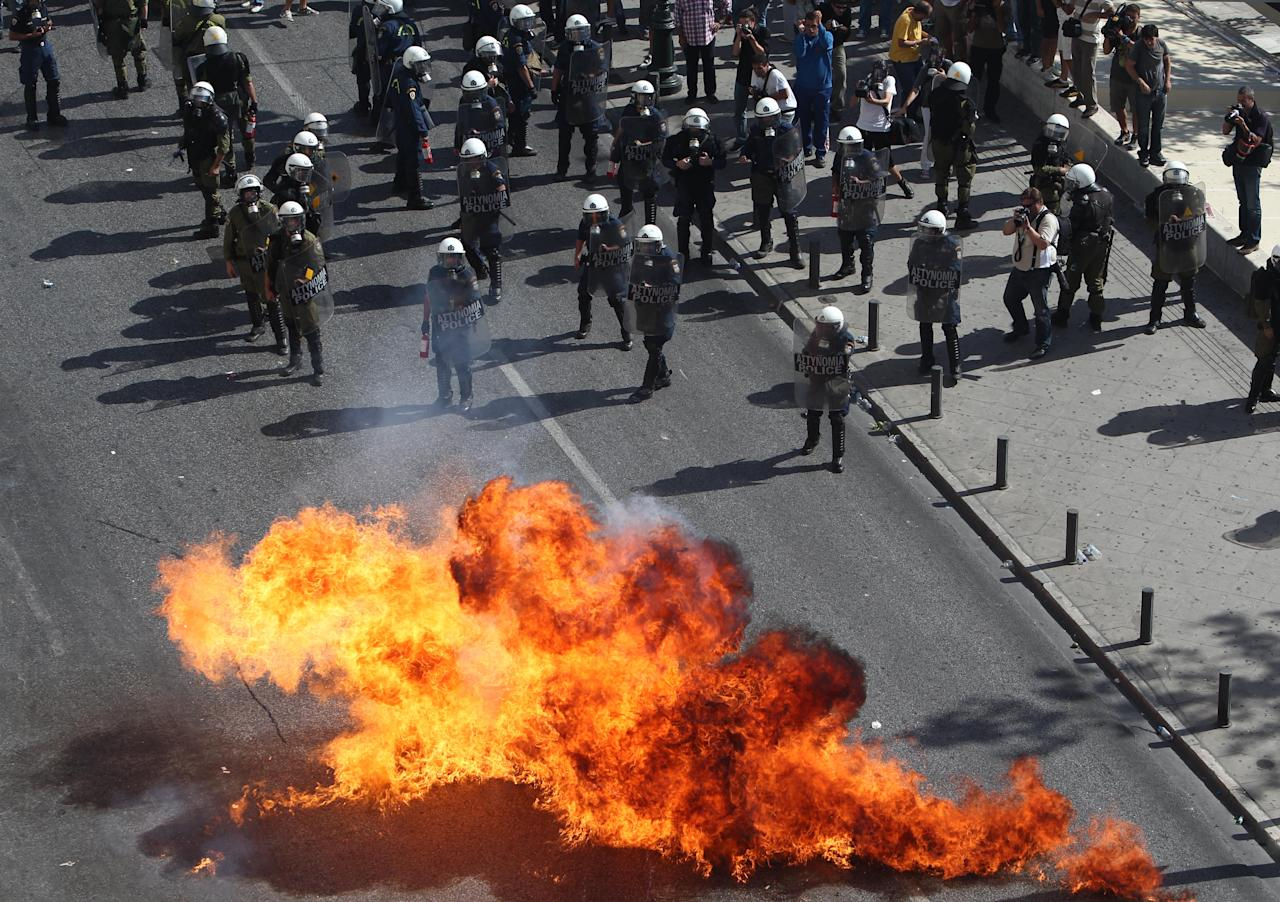 Protesters throw petrol bombs against riot police during a 24-hour nationwide general strike, Athens, Thursday, Oct. 18, 2012. Greece was facing its second general strike in a month Thursday as workers protested over another batch of austerity measures that are designed to prevent the bankruptcy of the country. (AP Photo/Thanassis Stavrakis)