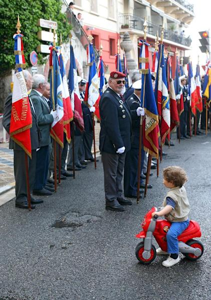 A child cycles past veterans of World War II as they take part in a ceremony in Nice, southeastern France, Wednesday, May 8, 2013, marking the 68th anniversary of the end of World War II in Europe. (AP Photo/Lionel Cironneau)