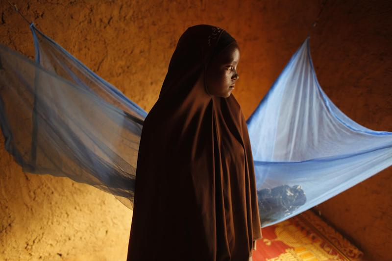 In this Wednesday July 18, 2012, photo, Zali Idy,12, poses in her bedroom in the remote village of Hawkantaki, Niger. Zali was married in 2011. In January 2012, soon after she turned 12, she was carried on a bullock cart to her 23-year-old husband's home. Her breasts had barely started to grow and she hadn't even had her first period. For several weeks, she refused to sleep with him, until the women in the village intervened, scolding her until she relented. Last year, before the start of the harvest, there were 10 girls in Hawkantaki between the ages of 11 and 15. By spring 2012, seven were married, and another two are engaged. (AP Photo/Jerome Delay)