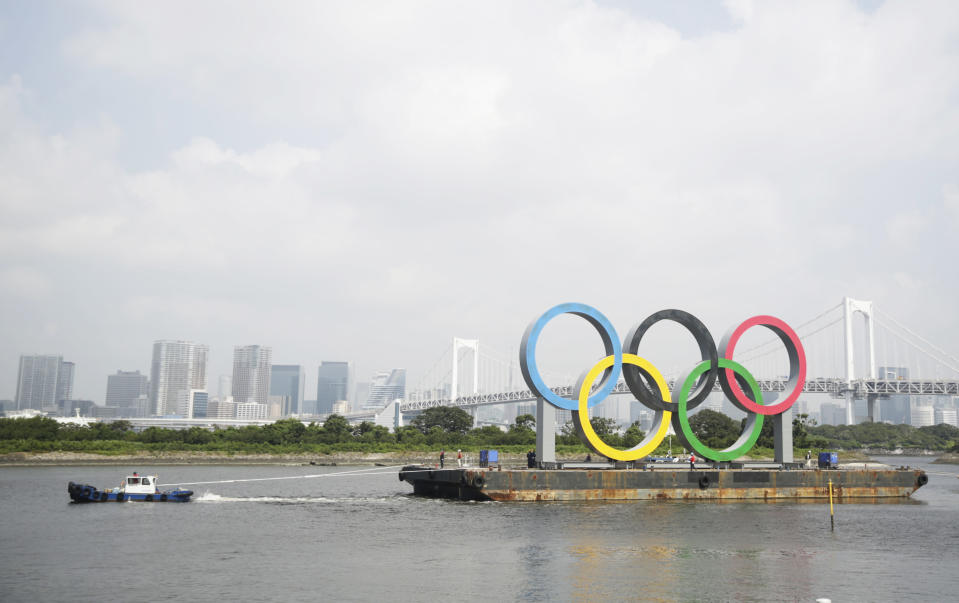 """A tugboat moves a symbol installed for the Olympic and Paralympic Games Tokyo 2020 on a barge moved away from its usual spot off the Odaiba Marine Park in Tokyo Thursday, Aug. 6, 2020. The five Olympic rings floating on a barge in Tokyo Bay were removed for what is being called """"maintenance,"""" and officials says they will return to greet next year's Games. The Tokyo Olympics have been postponed for a year because of the coronavirus pandemic and are to open on July 23, 2021. The Paralympics follow on Aug. 24. (AP Photo/Hiro Komae)"""