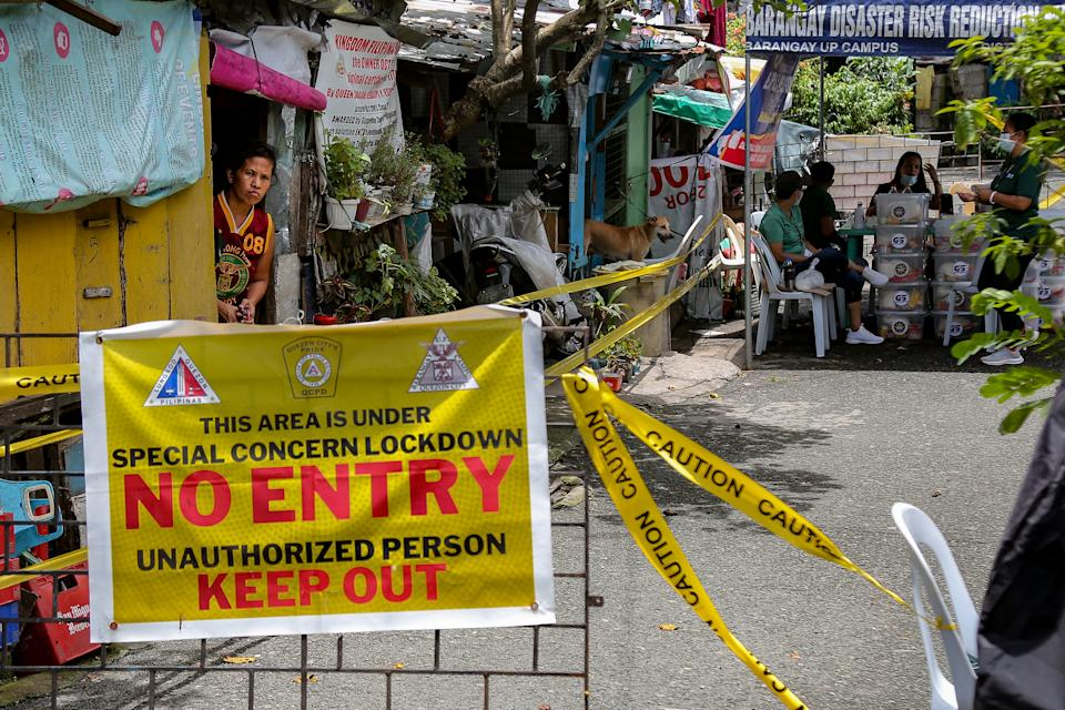 FILE PHOTO: A woman peeks through the door of her house as she waits for aid distribution inside a locked-down community in Quezon City, on August 6, 2021. (Photo: George Calvelo/NurPhoto via Getty Images)