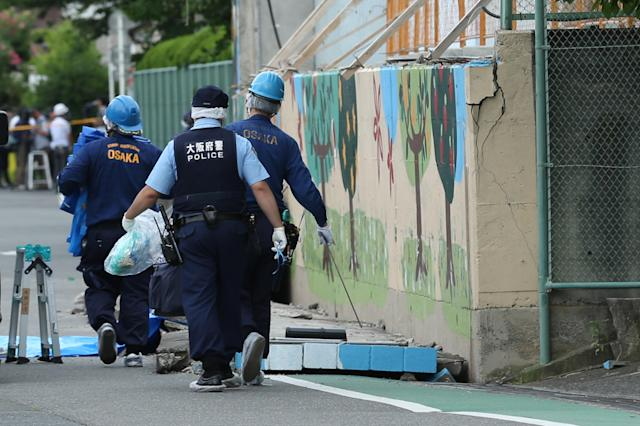 <p>Police officers investigate the site where an elementary school student was killed after the walls next to the school pool had collapsed due to a magnitude 6.1 earthquake in Takatsuki, Osaka, Japan, on Monday, June 18, 2018. (Photo: Buddhika Weerasinghe/Bloomberg via Getty Images) </p>