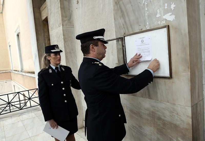 A police officer places outside the Greek parliament an anouncement of the parliament's dissolution in Athens on December 31, 2014 (AFP Photo/)