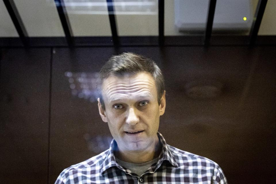 Russian opposition leader Alexei Navalny looks at photographers standing behind a grass of the cage in the Babuskinsky District Court in Moscow, Russia, Saturday, Feb. 20, 2021. A Moscow court has rejected Russian opposition leader Alexei Navalny's appeal against his prison sentence. Earlier this month, a lower court sentenced Navalny to two years and eight months in prison for violating terms of his probation while recuperating in Germany from a nerve agent poisoning that he blames on the Kremlin. (AP Photo/Alexander Zemlianichenko)