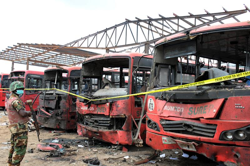 A photo taken on April 14, 2014 shows a soldier standing guard in front of burnt buses after an attack in Abuja, Nigeria