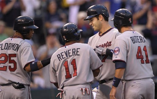 Minnesota Twins' Joe Mauer (7), second from right, is congratulated by teammates Pedro Florimon (25), Ben Revere (11) and Drew Butera (41) after driving them in iwth a grand slam to give the Twins a 8-2 lead in the second inning during the second baseball game of a doubleheader, Saturday, Sept. 1, 2012, in Kansas City, Mo. (AP Photo/Reed Hoffmann)