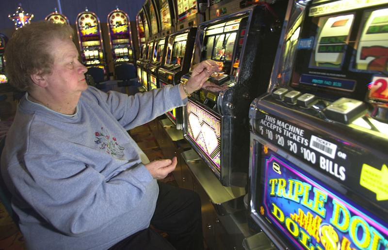 FILE - In this Dec. 13, 2003 file photo, Terry Skierczynski drops a quarter into a slot machine at the Seneca Niagara Casino in Niagara Falls, N.Y. The Seneca and Mohawk tribes have for years withheld casino payments to the state because they say New York violated contracts with them by allowing gambling in exclusive Indian territories. Consequently, the state stopped sending money _ more than $100 million so far _ to municipalities where Indian casinos operate. Without their share of casino money, these communities are straining to provide services. (AP Photo/David Duprey, File)