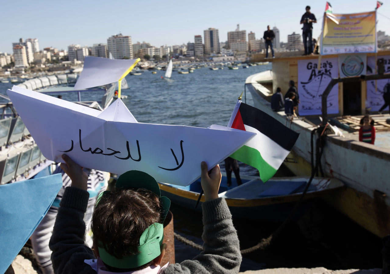 """A Palestinian girl holds up a paper boat with a """"No to Siege"""" written in Arabic at the fishermen's port in Gaza City, Saturday, Nov. 30, 2013 during a protest against Israel's naval blockade of Gaza. Israel and Egypt imposed air, sea and land blockade of Gaza Strip in 2007. (AP Photo/Adel Hana)"""