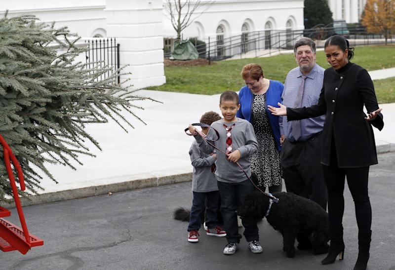 First lady Michelle Obama, right, acompanied by nephews Aaron, left, and Austin Robinson, and growers Mary and Dave Vander Velden, of Oconto, Wis., gestures as she receives the Official White House Christmas Tree at the White House in Washington, Friday, Nov. 25, 2016. The Balsam-Veitch fir is 19 feet tall and 12 feet wide. (AP Photo/Alex Brandon)