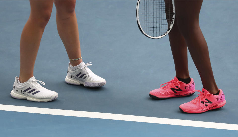 United States' Coco Gauff, right, and compatriot Caty McNally wear a tribute to Kobe Bryant on their shoes during their doubles match against Japan's Shuko Aoyama amd Ena Shibahara at the Australian Open tennis championship in Melbourne, Australia, Monday, Jan. 27, 2020. (AP Photo/Dita Alangkara)