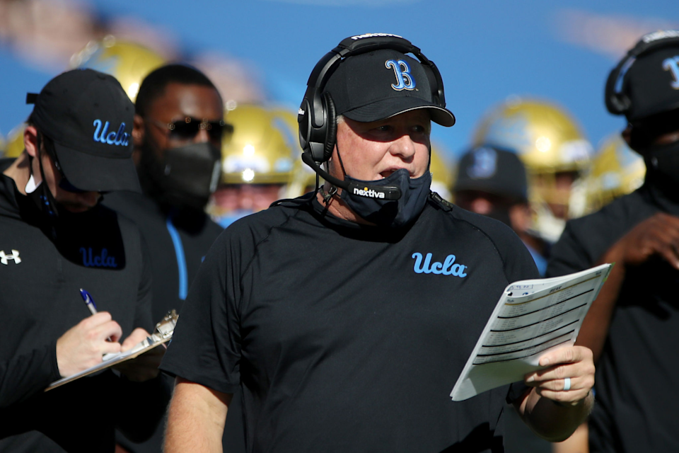 UCLA football coach Chip Kelly reads a play from a chart while standing on the sideline.