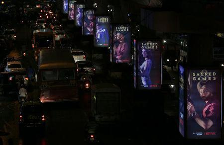 """Traffic moves on a road past hoardings of Netflix's new television series """"Sacred Games"""" in Mumbai, India, July 11, 2018. REUTERS/Francis Mascarenhas"""