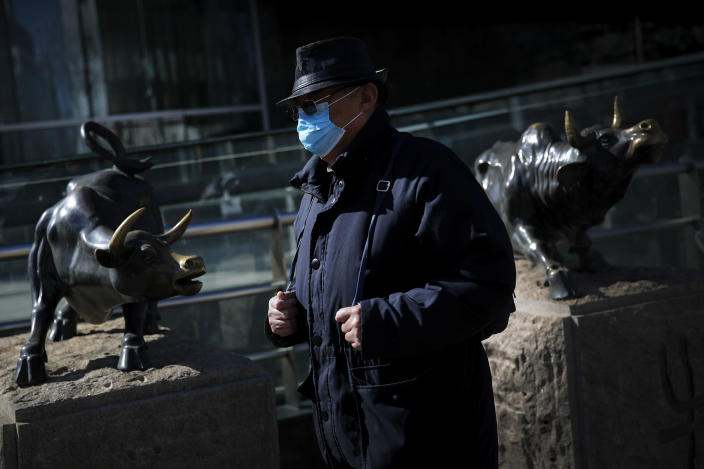 A man wearing a protective face mask walks by statues of bulls on display outside a bank in Beijing, Tuesday, March 10, 2020. Asian stock markets took a breather from recent steep declines on Tuesday, with several regional benchmarks gaining more than 1% after New York futures reversed on news that President Donald Trump plans to ask Congress for a tax cut and other quick measures to ease the pain of the virus outbreak. (AP Photo/Andy Wong)