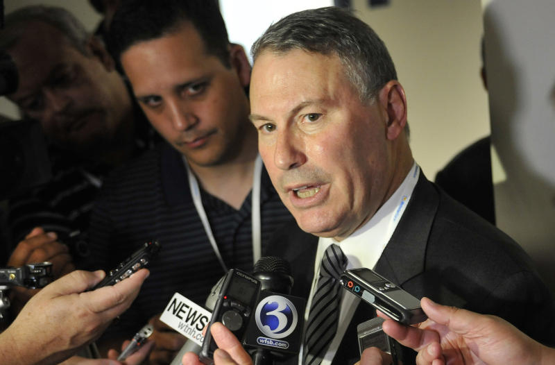 FILE - In this Aug. 30, 2012, file photo, Big East commissioner Mike Aresco answers questions from the media before an NCAA college football game between Connecticut and Massachusetts at Rentschler Field in East Hartford, Conn. Big East football schools will get almost all of a $110 million pot in a deal that will allow seven departing basketball schools to keep the name Big East and start playing in their own conference next season, a person familiar with the negotiations says. They will receive approximately $100 million under the agreement, most of which will go to holdover members Connecticut, South Florida and Cincinnati. (AP Photo/Jessica Hill, File)