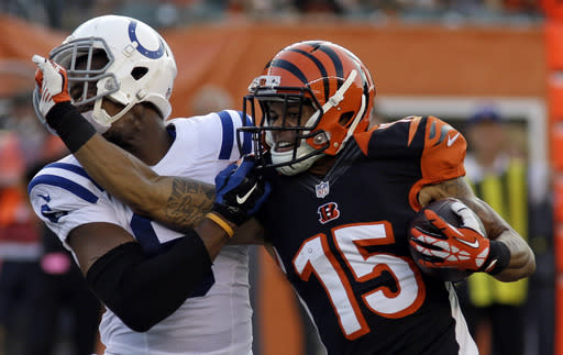Cincinnati Bengals wide receiver Colin Lockett (15) pushes off against Indianapolis Colts cornerback Loucheiz Purifoy in the first half of an NFL preseason football game, Thursday, Aug. 28, 2014, in Cincinnati. (AP Photo/Tom Uhlman)