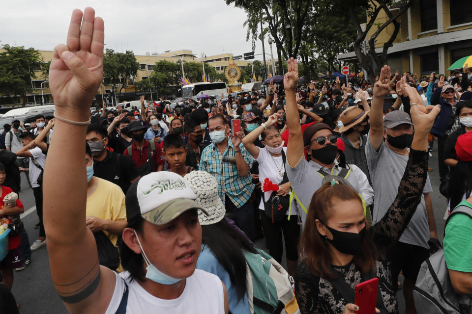 Anti-government protesters raise three-finger salutes, a symbol of resistance, during a protest near Democracy Monument in Bangkok, Thailand, Wednesday, Oct. 14, 2020. Thai activists hope to keep up the momentum in their campaign for democratic change with a third major rally in Bangkok on Wednesday. (AP Photo/Sakchai Lalit)