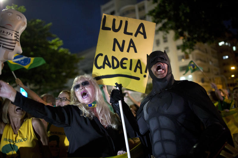 """FILE - In this April 3, 2018 file photo, a demonstrator dressed as Batman holds a sign that says in Portuguese: """"Lula in prison!"""" during a protest against Brazil's former President Luiz Inacio Lula da Silva on Copacabana beach in Rio de Janeiro, Brazil. Beginning in 2014, the so-called Carwash investigation has uncovered a colossal corruption scheme led to the jailing of several of the country's elite, from former Odebrecht CEO Marcelo Odebrecht to Lula. (AP Photo/Silvia Izquierdo, File)"""