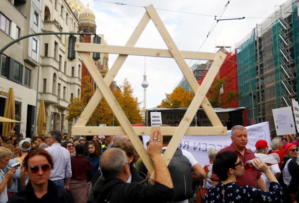 "A man carries a wooden Star of David as people attend a demonstration themed with the slogan ""#unteilbar"" (indivisible) to protest against antisemitism, racism and nationalism in Berlin, Germany, October 13, 2019. REUTERS/Hannibal Hanschke"