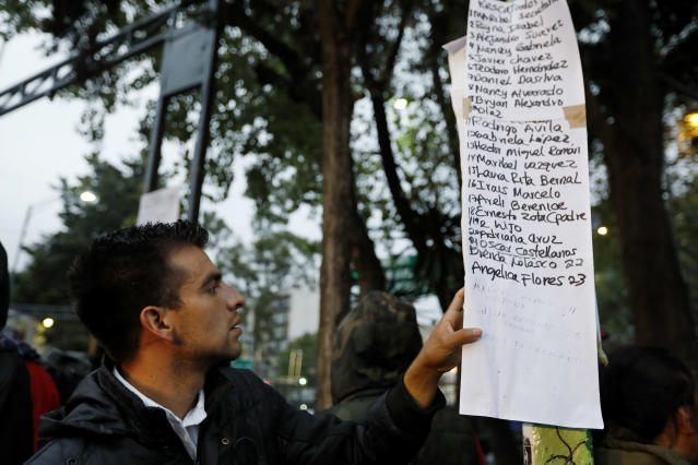 <p>People look for family and friends on a list of people rescued from an office building along Calle Alvaro Obregon in Colonia Condesa, in Mexico City, on Sept. 20, 2017. (Photo: Gary Coronado/Los Angeles Times via Getty Images) </p>