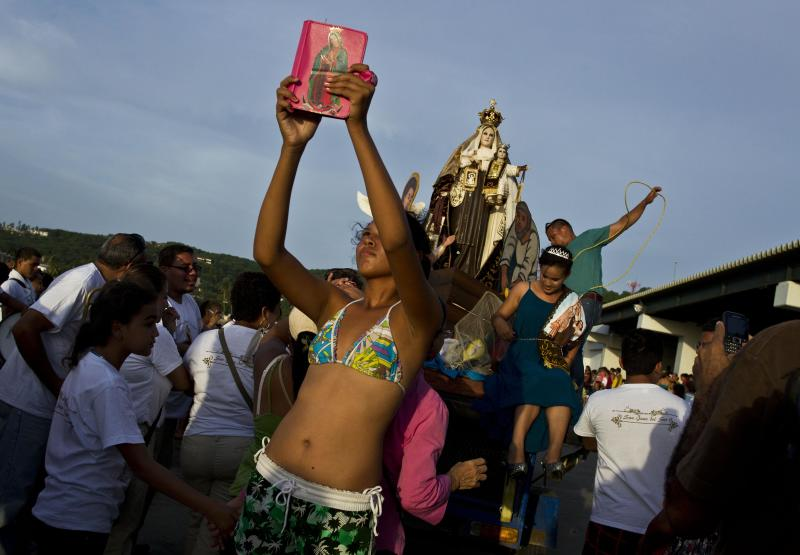 A young woman takes a picture with her tablet which is decorated by an image of the Virgin of Guadalupe during a religious procession of the Virgin of Carmen on the shores of the Pacific Ocean in San Juan del Sur, Nicaragua, Tuesday, July 16, 2013. Nicaragua's fishing community celebrate the feast day of the Virgin Carmen who is worshipped by Catholics as the patron saint of fishermen and sailors. (AP Photo/Esteban Felix)