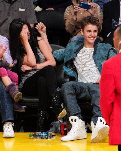 Singers Justin Bieber and girlfriend Selena Gomez had a night out courtside at the Lakers vs Spurs game last night at the Staples Center in Los Angeles. Gomez, a Texas native, was likely cheering on the San Antonio team (who won 112 to 91) when the couple were caught off guard by the Kiss Cam! A coy Gomez hid her face after seeing themselves on the jumbotron screen. An eyewitness said the crowd was going nuts!