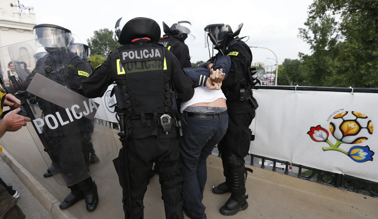 Polish riot police detain a Russian soccer fan prior to the Group A Euro occer championship match between Poland and Russia in Warsaw, Poland , Tuesday, June 12, 2012. (AP Photo/Czarek Sokolowski)