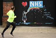 Street art depicting the logo of Britain's National Health Service (NHS), amid an outpouring of thanks to NHS staff treating COVID-19 patients, is painted on the gate of a shuttered pub in Pontefract