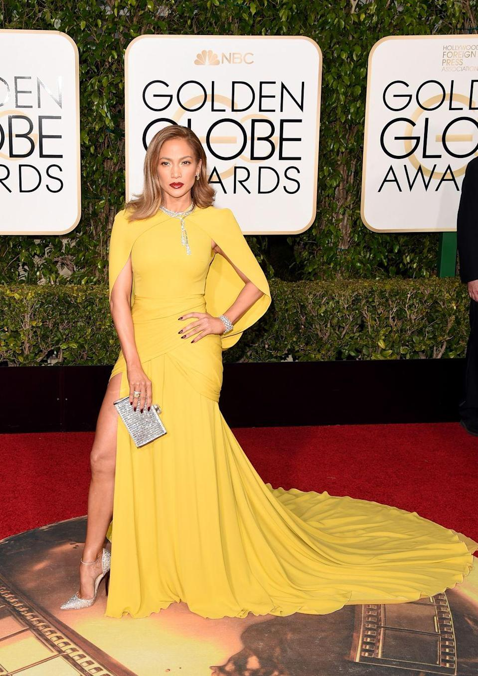 <p>Showing that she's a master of versatility in a yellow mustard cape dress by Giambattista Valli.</p>