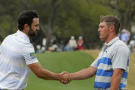 Antoine Rozner, of France, shakes hands with Bryson DeChambeau, right, after Rozner won the match on the 18th hole during a first round match at the Dell Technologies Match Play Championship golf tournament Wednesday, March 24, 2021, in Austin, Texas. (AP Photo/David J. Phillip)