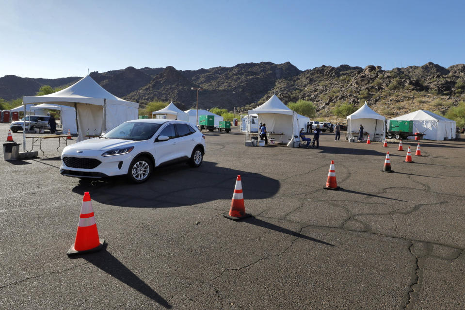 Just two vehicles of people utilize the COVID-19 Coronavirus testing site Tuesday, July 28, 2020 at South Mountain Park in Phoenix as other testing tents sit idle. It was the last day of a 12-day blitz aimed at bringing tens of thousands of COVID-19 tests to underserved Latino communities in Phoenix but only 14,000 of some 55,000 tests were administered at the park and the western neighborhood of Maryvale, leaving more than 40,000 COVID-19 test kits unused. (AP Photo/Matt York)
