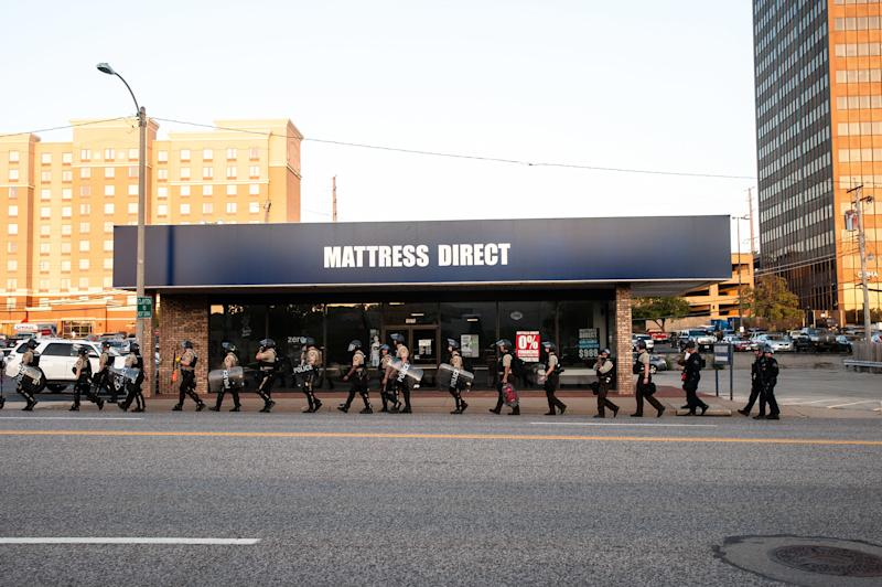 Riot police leave the scene of the protest in Clayton, a St. Louis suburb. (Joseph Rushmore for HuffPost)