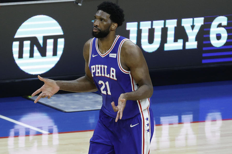 Joel Embiid shrugs his arms during a game.