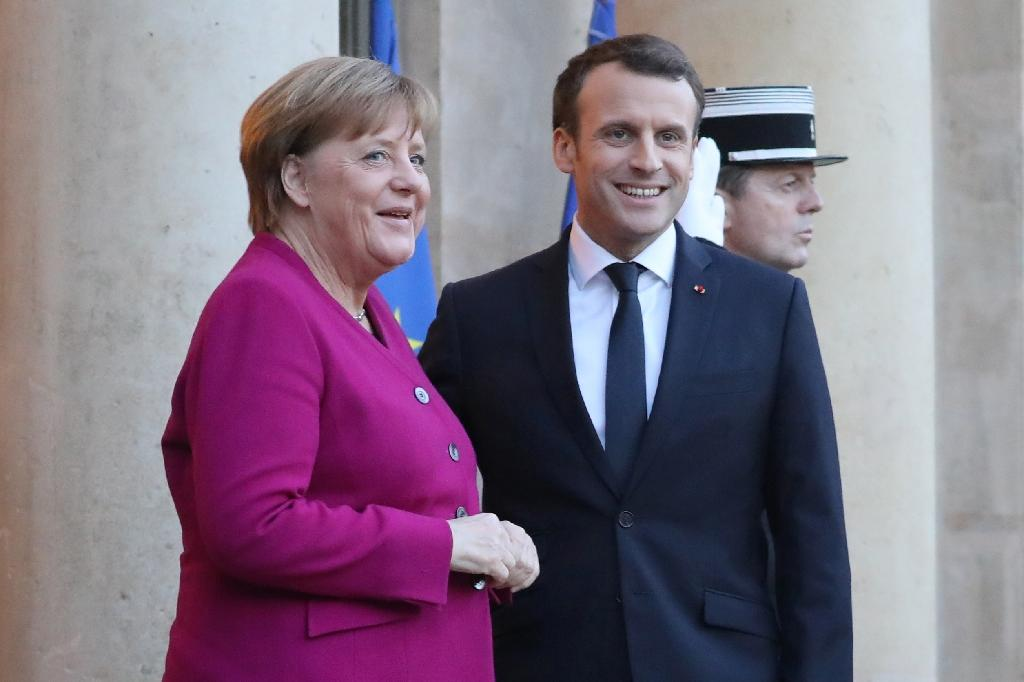 French president Emmanuel Macron welcomes German Chancellor Angela Merkel at the Elysee Palace in Paris (AFP Photo/LUDOVIC MARIN)