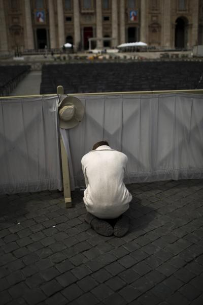 A worshiper prays in St. Peter's Square at the Vatican, Saturday, April 26, 2014. Pilgrims and faithful are gathering in Rome to attend Sunday's ceremony at the Vatican where Pope Francis will elevate in a solemn ceremony John XXIII and John Paul II to sainthood. (AP Photo/Emilio Morenatti)