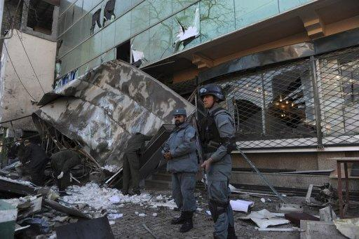 Afghan policemen stand guard at the site of a suicide attack at the gates of the Kabul City Centre shopping mall in Kabul on Monday. A Taliban suicide bomber targeted the popular mall, killing two guards and wounding at least two other people, officials say