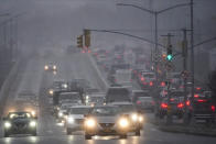Cars move along Woodhaven Blvd. as snow starts to fall Wednesday, Dec. 16, 2020, in the Queens borough of New York. (AP Photo/Frank Franklin II)