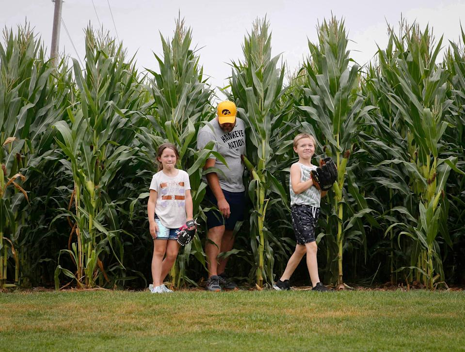 Eric Suiter of Bellevue steps out of the cornfield with his children Eli, 8, and Clara, 6, at the Field of Dreams in Dyersville on Thursday, Aug. 5, 2021. The field and movie site has seen increased popularity in recent weeks due to an upcoming Major League Baseball game between the Chicago White Sox and the New York Yankees.