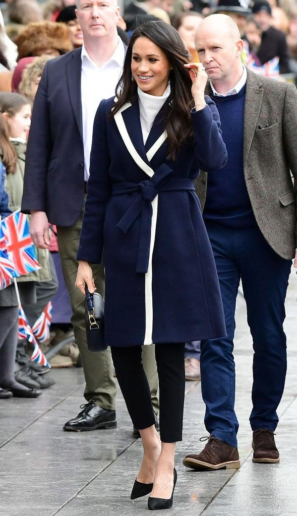 """<p>To mark International Women's Day, Prince Harry and Meghan Markle travelled to Birmingham on March 8, 2018. The soon-to-be newlyweds visited a project designed to inspire girls to pursue careers in science, tech, engineering and mathematics. <br>For the event, Meghan opted for a navy wrap-around coat by <a rel=""""nofollow noopener"""" href=""""https://www.net-a-porter.com/gb/en/product/975199?cm_mmc=LinkshareUK-_-TnL5HPStwNw-_-Custom-_-LinkBuilder&siteID=TnL5HPStwNw-XffqHyILq0xc522xrjm4Kw&Skimlinks.com=Skimlinks.com"""" target=""""_blank"""" data-ylk=""""slk:J. Crew"""" class=""""link rapid-noclick-resp"""">J. Crew</a> (FYI, it's still available) and teamed the look with a <a rel=""""nofollow noopener"""" href=""""https://www.matchesfashion.com/products/1152595?qxjkl=tsid:30065