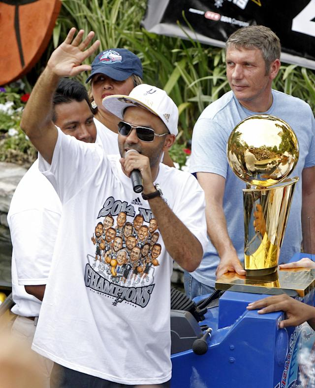 San Antonio's Tony Parker waves to the crowd during the Spurs' parade and celebration of their 5th NBA Championship in San Antonio, Texas, Weds., June 18, 2014