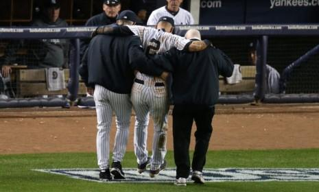 New York Yankee Derek Jeter is carried off of the field by trainer Steve Donohue, right, and manager Joe Girardi after injuring his leg during Game 1 of the American League Championship series against the Detroit Tigers.