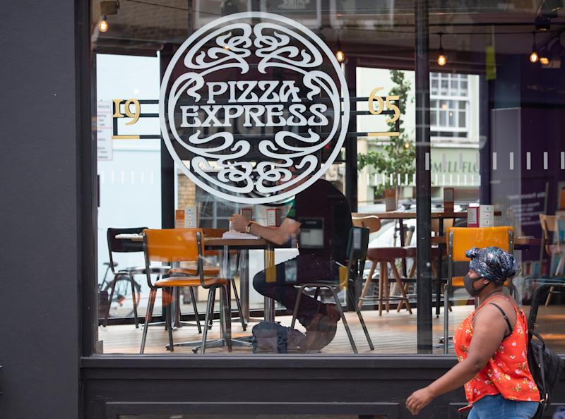 A woman passes a branch of Pizza Express in London, as the restaurant chain has said it could close around 67 of its UK restaurants, with up to 1,100 jobs at risk, as part of a major restructuring plan. (Photo by Dominic Lipinski/PA Images via Getty Images)