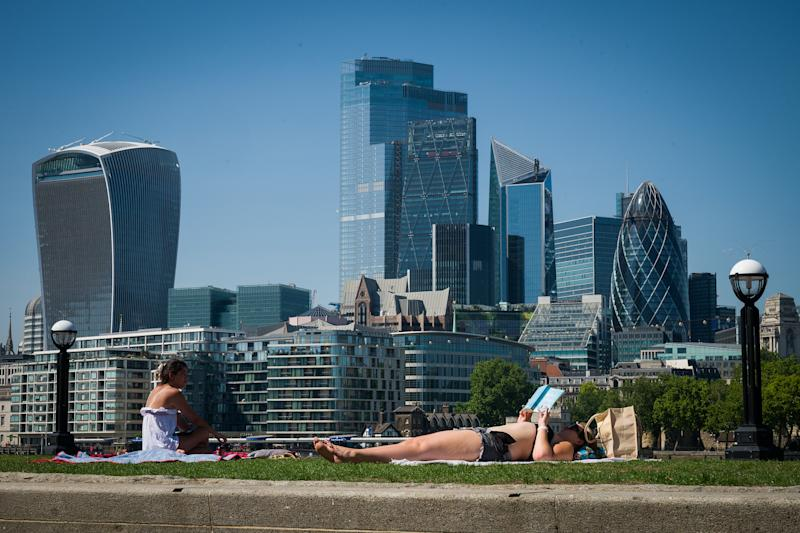 LONDON, UNITED KINGDOM - JUNE 24: People sunbathe on the park near Tower Bridge as the City of London is seen in the background on June 24, 2020 in London, United Kingdom. The UK is experiencing a summer heatwave, with temperatures in many parts of the country expected to rise above 30C and weather warnings in place for thunderstorms at the end of the week. (Photo by Leon Neal/Getty Images)