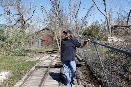 FILE PHOTO: Jim Broaddus, director of the Bear Creek Feline Center, stands on a fence flattened by Hurricane Michael at the Feline Center in Panama City, Florida, U.S. October 12, 2018. REUTERS/Terray Sylvester/File Photo