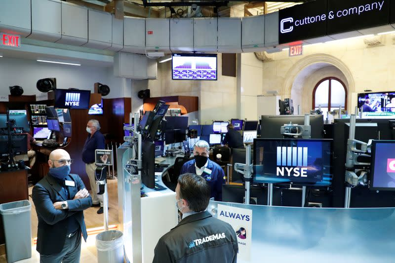 Traders wearing masks work, on the first day of in person trading since the closure during the outbreak of the coronavirus disease (COVID-19) on the floor at the NYSE in New York