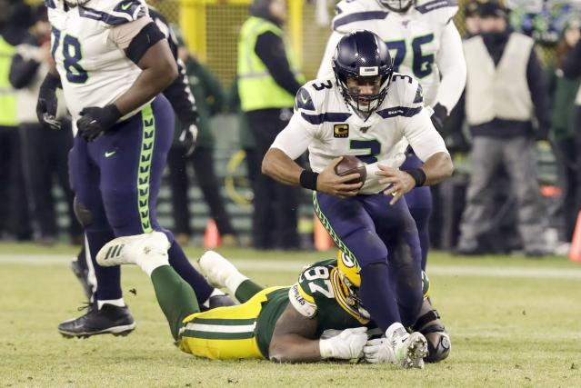 Seattle Seahawks' Russell Wilson gets away from Green Bay Packers' Kenny Clark during the first half of an NFL divisional playoff football game Sunday, Jan. 12, 2020, in Green Bay, Wis. (AP Photo/Darron Cummings)