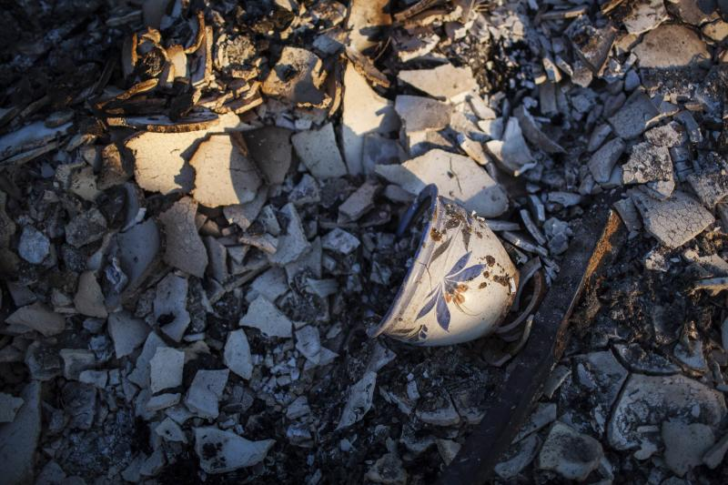 A pot is seen among debris at a house destroyed by the Clover Fire in Happy Valley