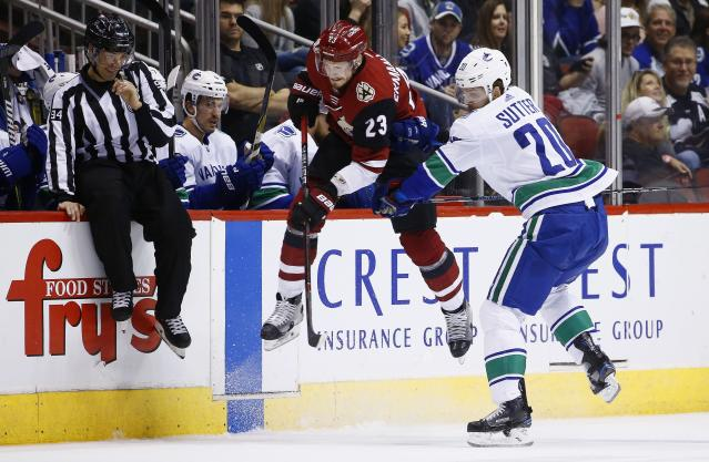 Vancouver Canucks center Brandon Sutter (20) checks Arizona Coyotes defenseman Oliver Ekman-Larsson (23) into the boards as linesman Bryan Pancich (94) braces for the hit during the first period of an NHL hockey team Sunday, March 11, 2018, in Glendale, Ariz. (AP Photo/Ross D. Franklin)