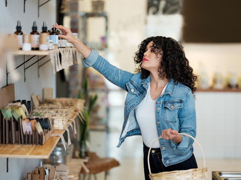 A beautiful latin young woman shopping with a basket in a zero waste store and reaching for some products.